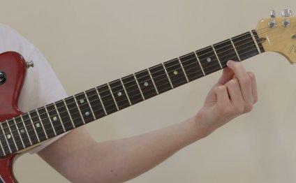 Man placing finger on guitar